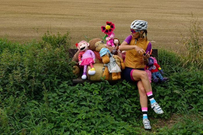 Oderske vrchy. Dziewczyna w stroju kolarskim siedząca na ławce obok pluszowych zwierzątek