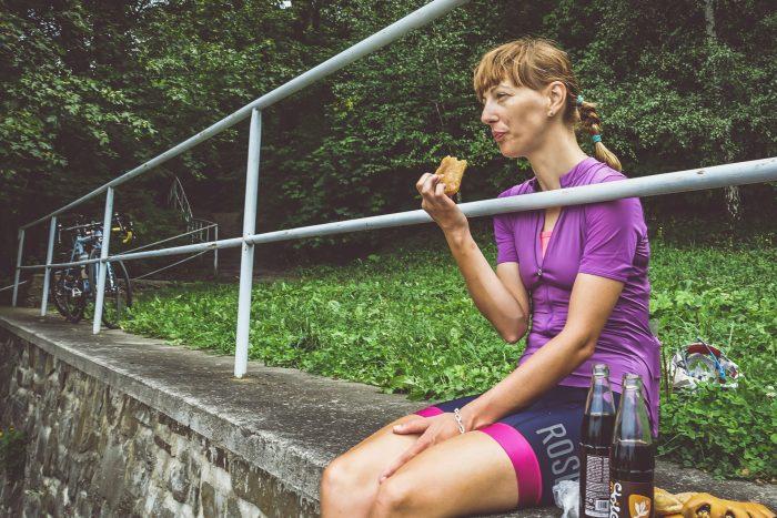 Oderske vrchy. Dziewczyna w stroju kolarskim jedząca ciastko