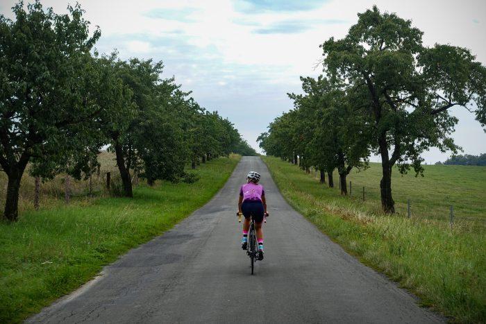 Oderske vrchy. Dziewczyna jadąca drogą wśród drzew owocowych