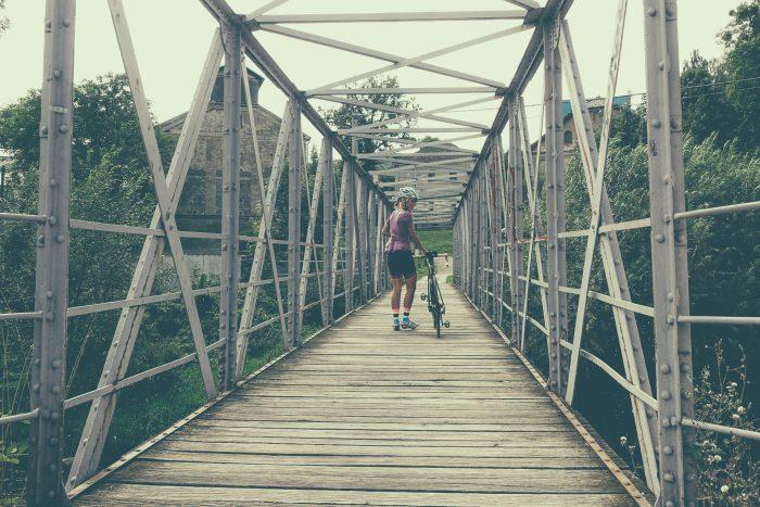 Oderske vrchy. Dziewczyna z rowerem na kładce nad rzeką