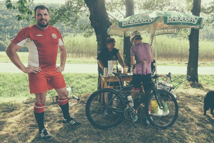 Oderske vrchy. Piłkarz, dziewczyna z rowerem i kobieta sprzedająca napoje na wiejskim boisku