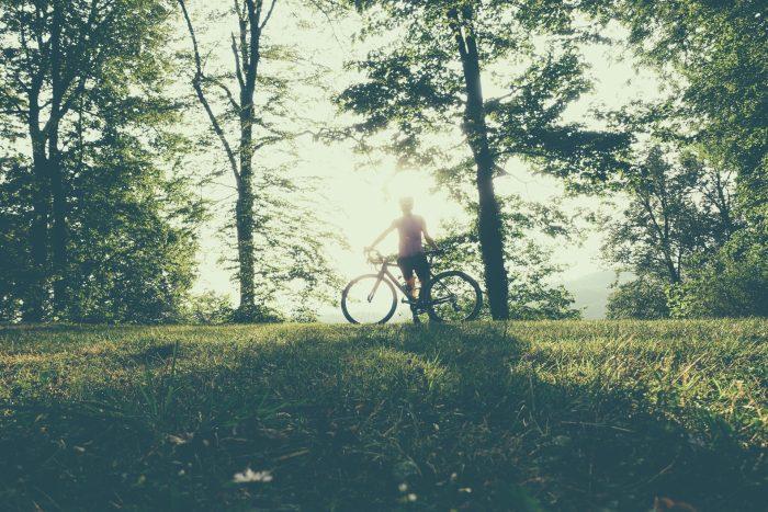 Oderske vrchy. Dziewczyna na rowerze sfotografowana pod słońce
