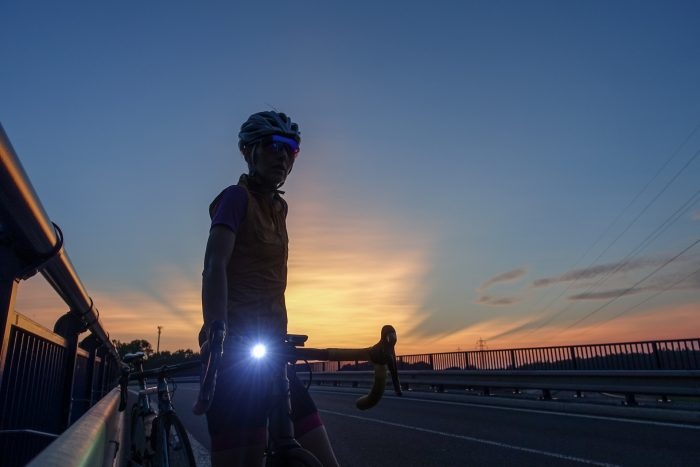 Oderske vrchy. Dziewczyna na rowerze o zmierzchu z zapaloną lampką na kierownicy