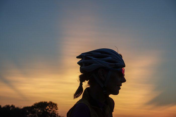 Oderske vrchy. Dziewczyna w kolarskim kasku na tle żółtego nieba