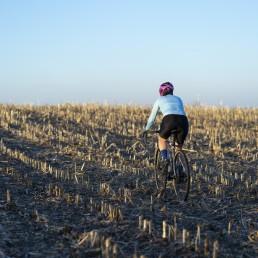 sport. dziewczyna na rowerze jadąca po polu kukurydzy